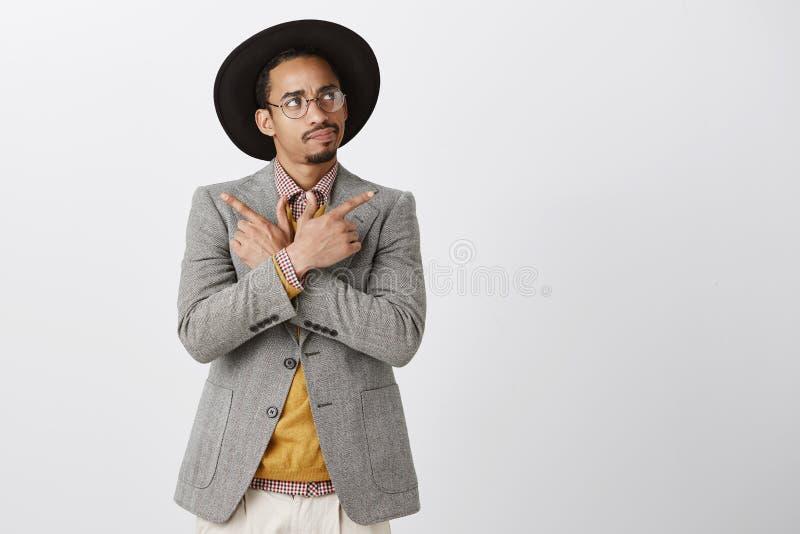 Hora de fazer a decisão Retrato do homem de pele escura atrativo duvidoso focalizado no chapéu negro e no revestimento, mãos de c imagens de stock royalty free