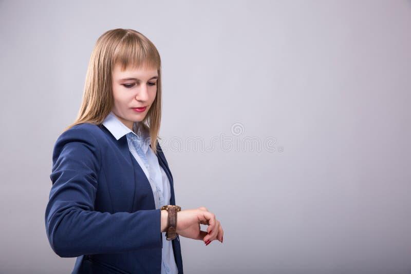 Hora de hacer negocio Mujer joven pensativa en ropa de sport elegante que comprueba el tiempo Mirada modelo al reloj foto de archivo libre de regalías