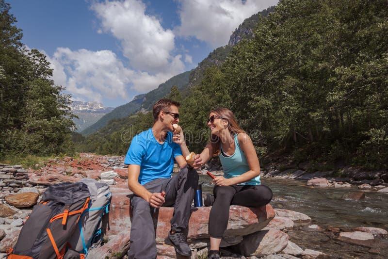 Hora de la almuerzo de los pares de los Backpackers con el landjaeger y pan en un río foto de archivo libre de regalías