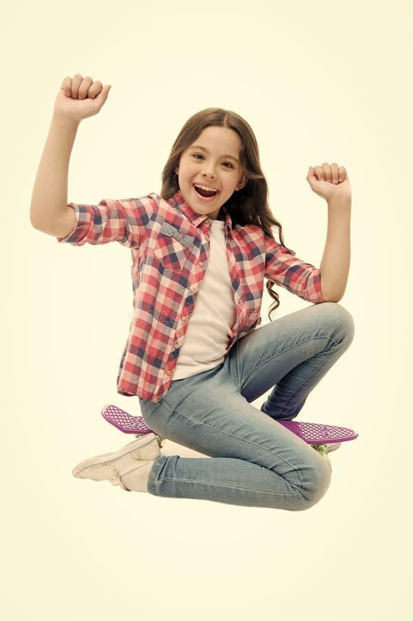 Hora de montar A menina da criança entusiasmado senta a placa da moeda de um centavo Passatempo adolescente moderno A cara feliz  fotografia de stock