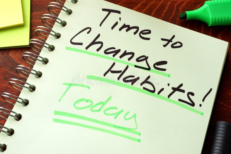 Hora de mudar os hábitos escritos hoje em um bloco de notas fotos de stock