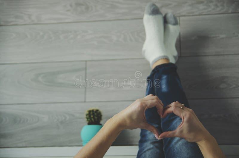 Hora de relajarse Ama de casa o mujer joven que miente con sus piernas para arriba en cama en el dormitorio y que forma una forma fotografía de archivo libre de regalías