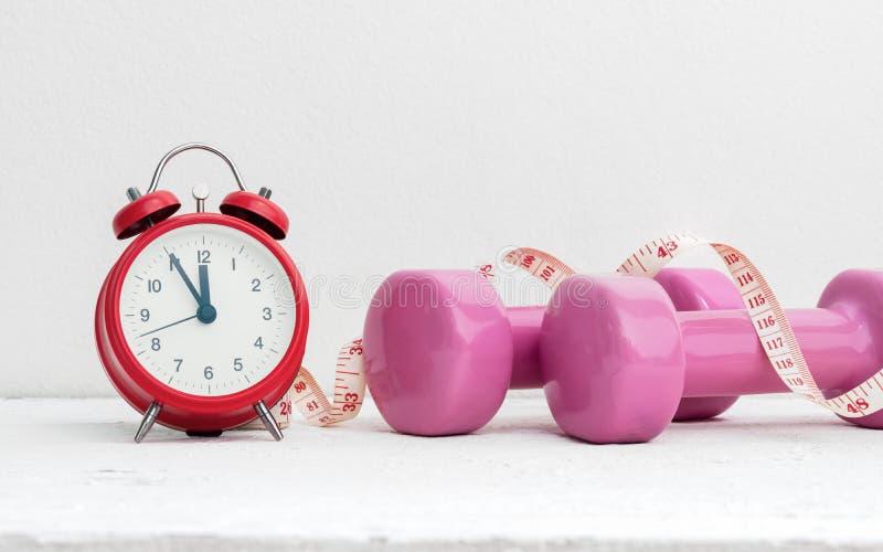 Hora de resolverse, forma de vida y concepto sanos de la dieta Dumbb rosado imagen de archivo