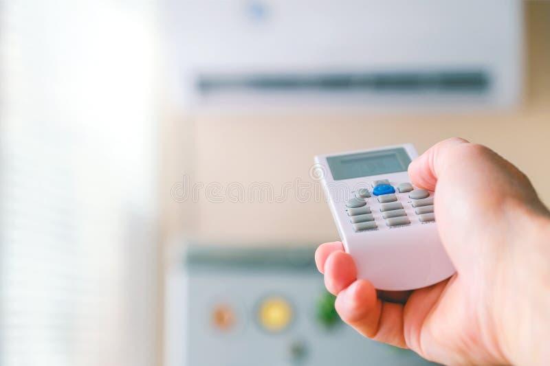 Hora de selecionar Mão masculina com controlo a distância do condicionamento de ar O homem comuta os modos de acondicionamento Re fotos de stock royalty free