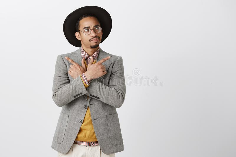 Hora de tomar la decisión Retrato del varón de piel morena atractivo dudoso enfocado en el sombrero negro y la chaqueta, manos qu imágenes de archivo libres de regalías
