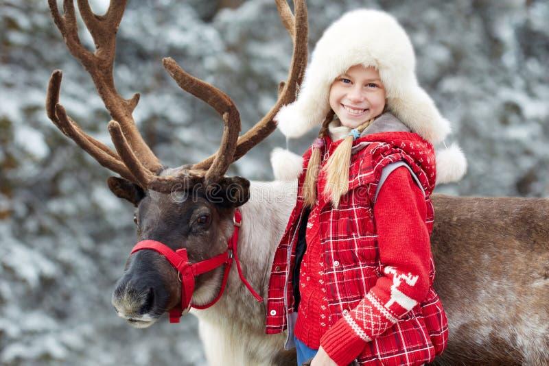 Hora del recreo del invierno Niña feliz que abraza su reno imagen de archivo libre de regalías