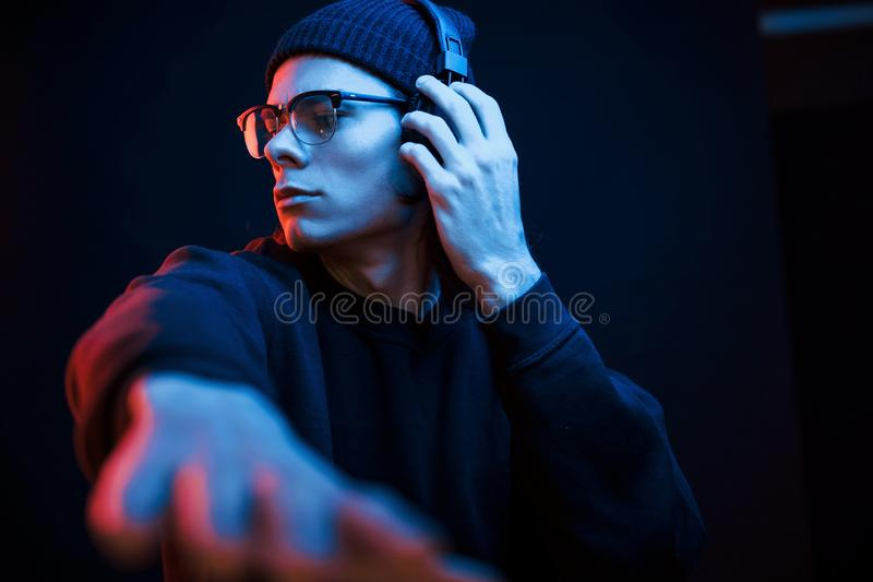 Hora do partido Estúdio fotografado em estúdio escuro com luz neon Retrato de homem sério imagens de stock