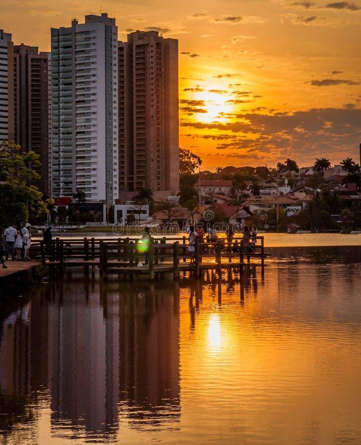 A hora dourada com construções refletiu na água de um lago em um parque Alguns povos na plataforma dos parques que apreciam a vis fotografia de stock royalty free