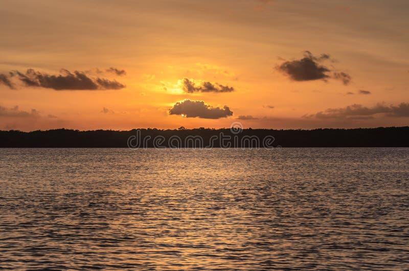 Hora dourada em um por do sol bonito sobre águas de um rio, nuvens sobre o sol imagens de stock