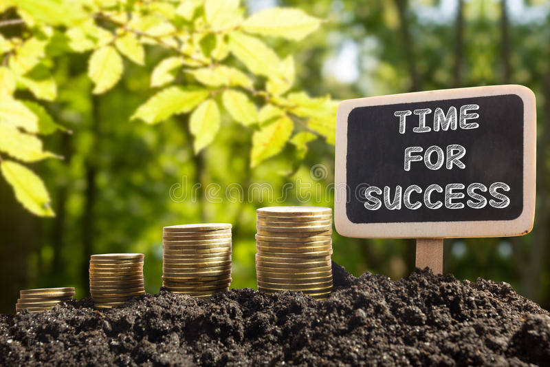 Hora para el éxito - concepto financiero de la oportunidad Monedas de oro en pizarra del suelo en fondo natural borroso imagenes de archivo