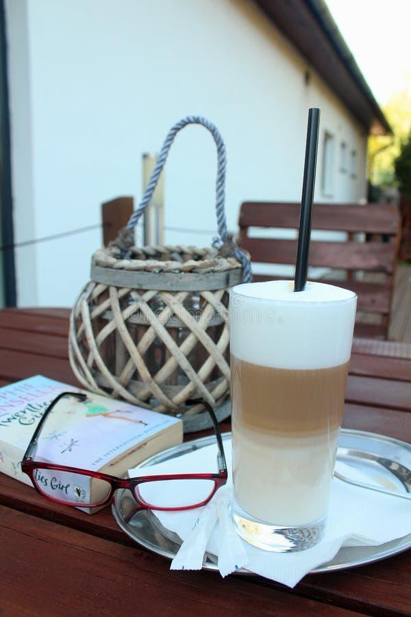 Hora para el café - latte del caffe en un restaurante mientras que se relaja con un libro imagen de archivo libre de regalías