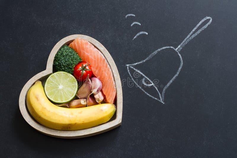 Hora para el concepto de la comida de la dieta del extracto del corazón de la salud en la pizarra con la campana imagen de archivo libre de regalías