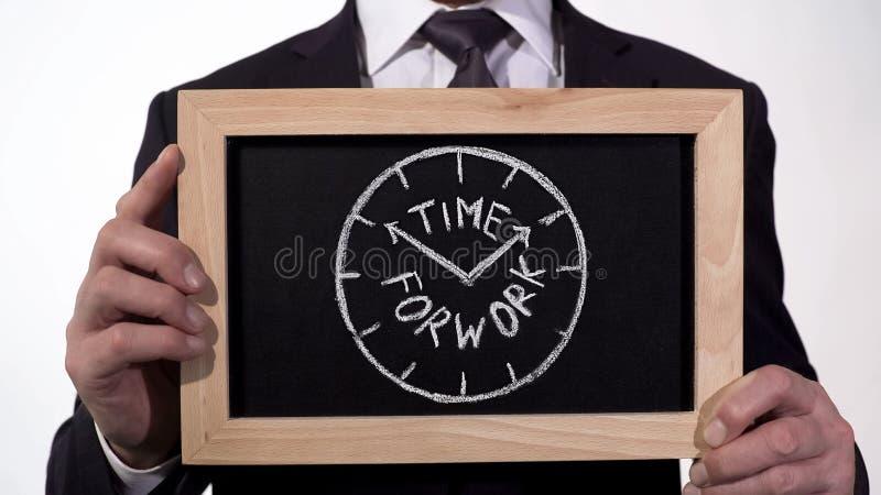 Hora para el reloj del trabajo dibujado en la pizarra en manos del hombre de negocios, planeamiento del horario foto de archivo