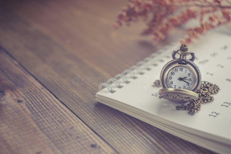 Hora para esperar com o relógio de bolso do vintage no calendário e no W imagem de stock