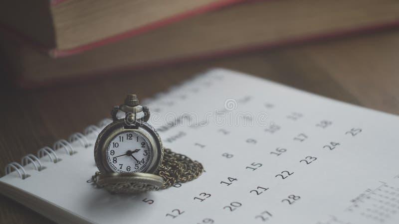 Hora para esperar con el reloj de bolsillo del vintage en el calendario y el W foto de archivo libre de regalías