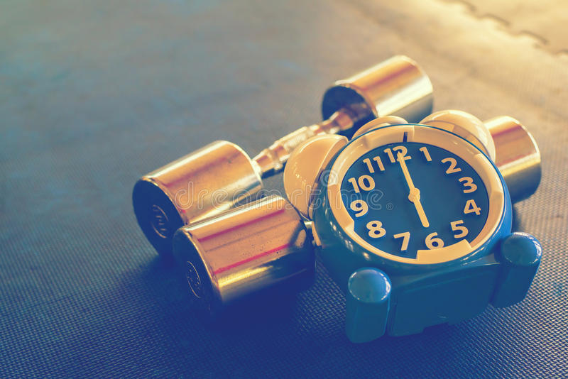 Hora para exercitar o despertador e o peso o fundo do Gym Conceito saudável do tempo da parte fotografia de stock royalty free