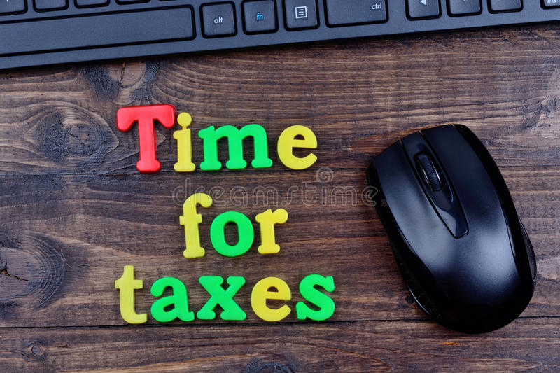 Hora para las palabras de los impuestos en la tabla imágenes de archivo libres de regalías