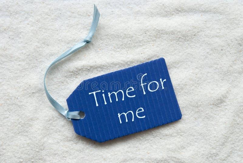 Hora para mim no fundo azul da areia da etiqueta imagem de stock