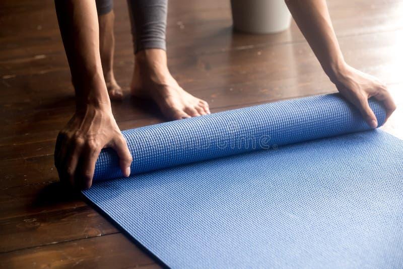 Hora para a prática, mãos fêmeas que desenrolam a esteira azul da ioga imagem de stock