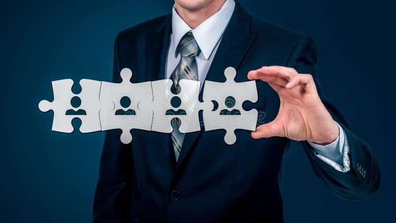 Hora - Recursos humanos - concepto del negocio con el hombre de negocios y el rompecabezas de la mano foto de archivo libre de regalías