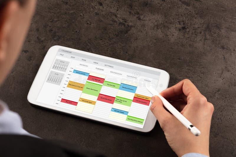 Horario de la mujer de negocios su programa sobre la tableta fotos de archivo libres de regalías