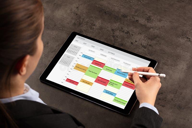 Horario de la mujer de negocios su programa sobre la tableta foto de archivo