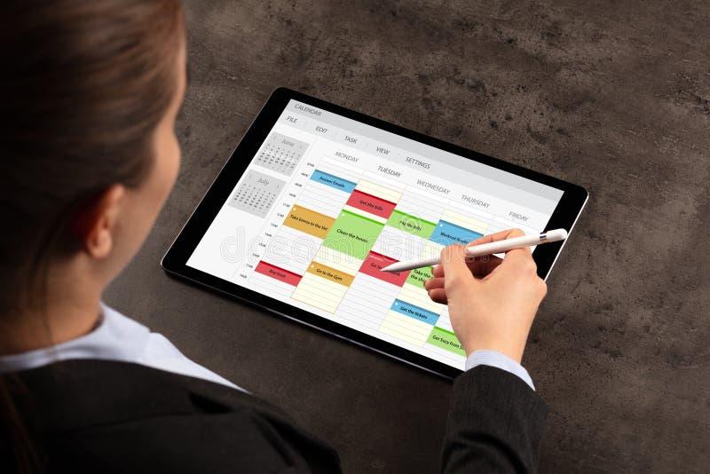 Horario de la mujer de negocios su programa sobre la tableta imágenes de archivo libres de regalías