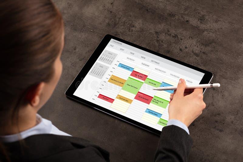 Horario de la mujer de negocios su programa sobre la tableta imagen de archivo