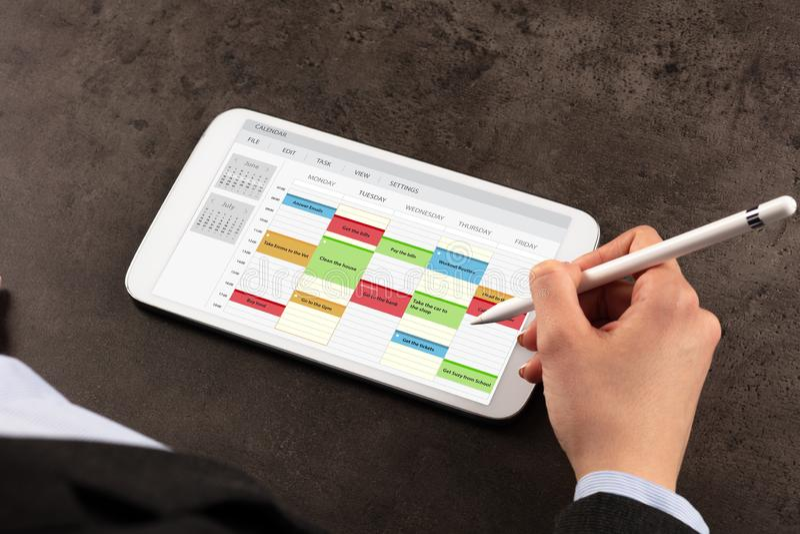 Horario de la mujer de negocios su programa sobre la tableta foto de archivo libre de regalías
