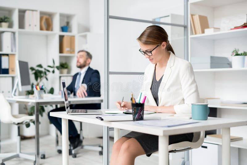 Horario de planificación de la señora atractiva ocupada en oficina imagen de archivo