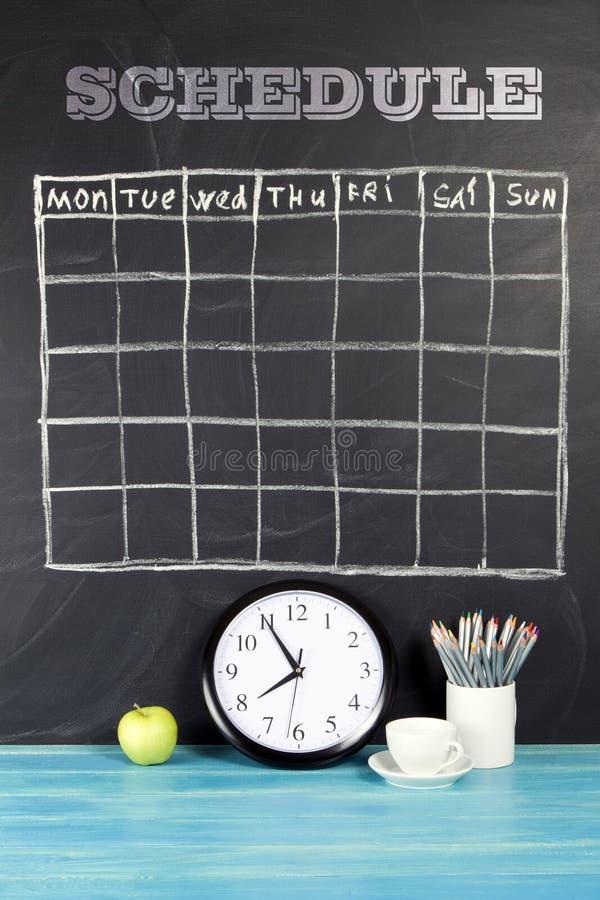 Horario del calendario de la rejilla en fondo negro de la pizarra imágenes de archivo libres de regalías