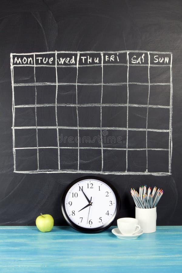 Horario del calendario de la rejilla en fondo negro de la pizarra fotografía de archivo libre de regalías