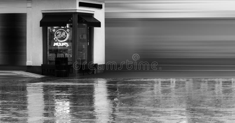 24 horas abiertas de señal de neón en una ventana del restaurante con los toldos italianos D?a lluvioso del verano imagen de archivo libre de regalías