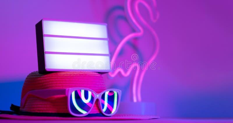 Horas de verão com a caixa leve vazia no chapéu com rosa de néon do flamingo do refection dos óculos de sol e luz azul e verde na fotografia de stock