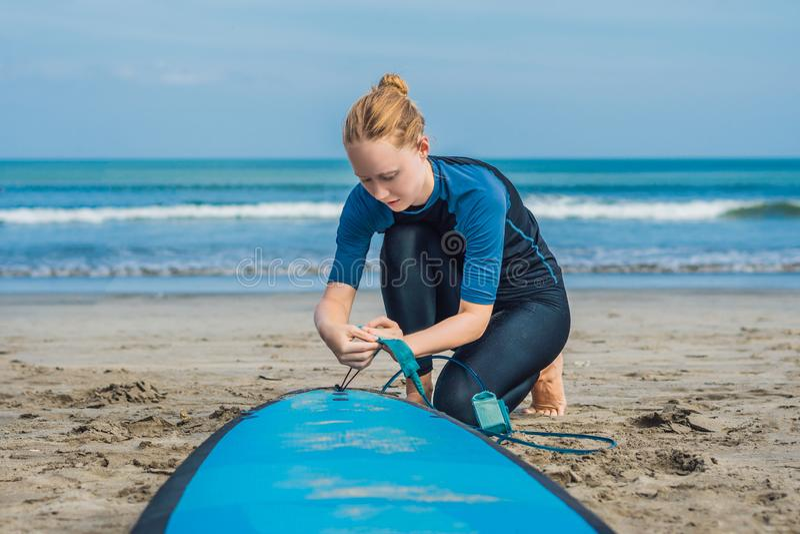 Horas de verão e conceito ativo do resto O novato novo da mulher do surfista prende a trela através do pé, indo surfar em barral  fotografia de stock