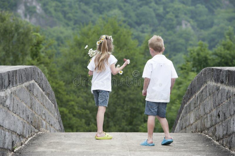 Horas de verão: menina do rapaz pequeno @ que corre em uma ponte imagens de stock