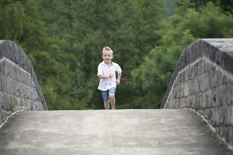 Horas de verão: rapaz pequeno que corre em uma ponte imagens de stock