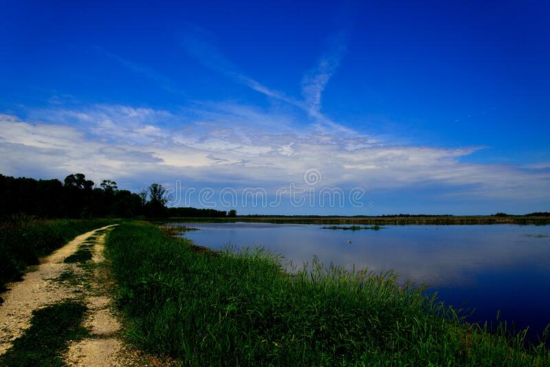 Horicon Marsh Drive and Walkway around the Water. A footpath and small access road around the water at Horicon Marsh, Wisconsin with beautiful reflective blue royalty free stock image