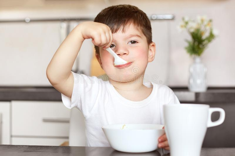 Horiontal portrait of attractive male child eats delicious porridge with milk, dressed in casual white t shirt, has good appetite stock photos