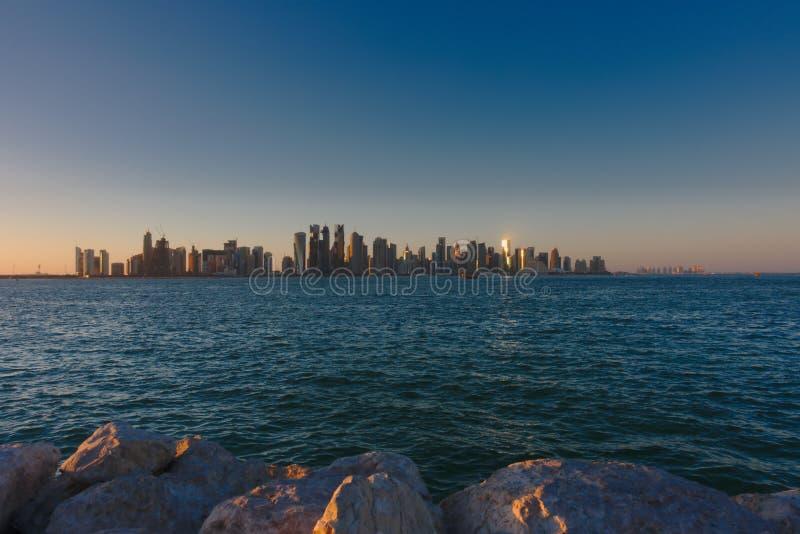 Horisont av den västra fjärden, på solnedgången från Dhowhamnen doha qatar arkivbilder