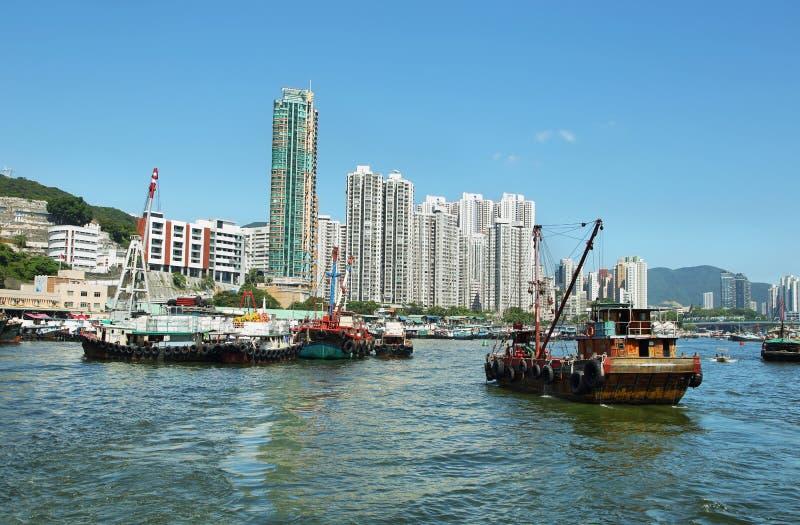 Horisont av skyskraporna och fiskebåtarna i den Aberdeen pir av Hong Kong royaltyfri fotografi