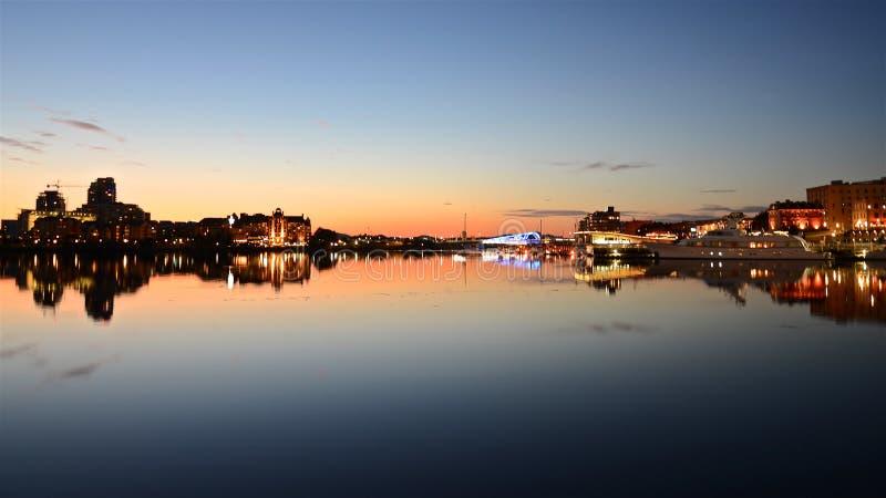 Horisont med de ljusa aftonljusen av Victoria City och solnedgångstrålar ljus bildar en spegelbild på vattnet av fjärden arkivfoto