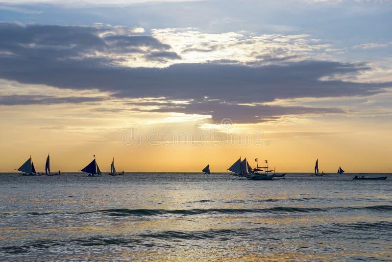 Horisont med segling och katamarankontur över havet på solnedgången royaltyfria bilder