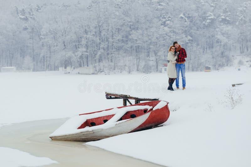 Horisontalälska par som ler det lyckliga krama fartyget, övervintrar den snöig ängen Forest Isolted Christmas New Year royaltyfri fotografi