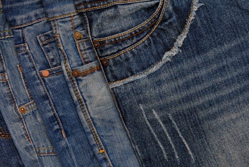 Horisontal denim background, assortment of blue jeans, pile of b royalty free stock photo