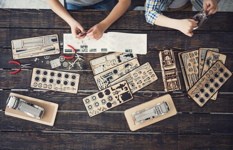 Horisontalbild av två pojkar som gör försiktigt mekanism arkivfoton