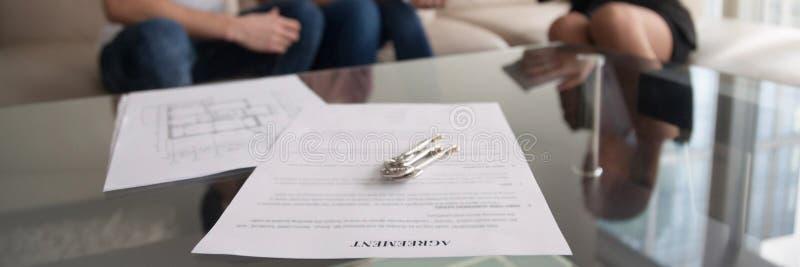 Horisontalbildparet möter fastighetsmäklaren för underteckning av uthyrnings- överenskommelse royaltyfri bild