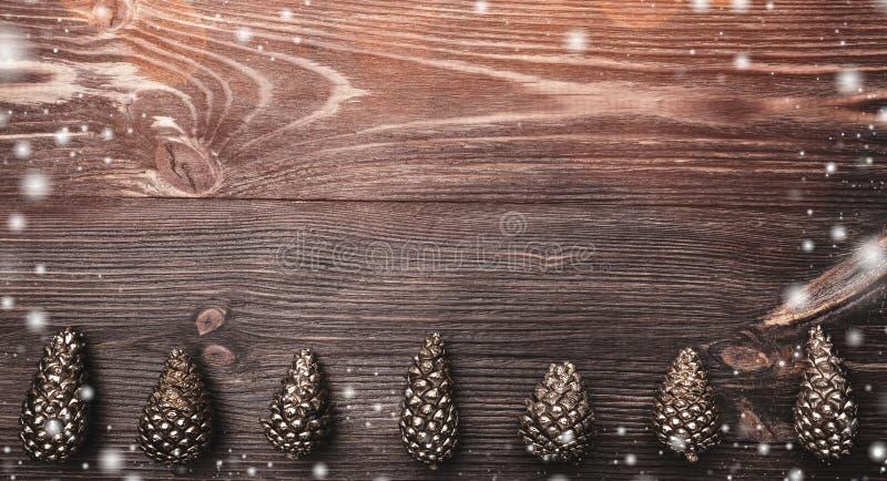 Horisontalbrun wood bakgrund med längst ner guld- kottar Semestra utrymme för vinter, xmas, ferier för nytt år och jul arkivbild