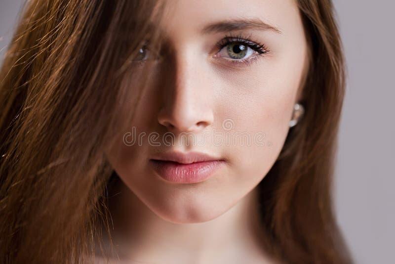 Horisontalcloseupstående av en härlig ung kvinna med ren hud, långa ögonfrans och naturlig skönhet, ny framsida arkivfoto