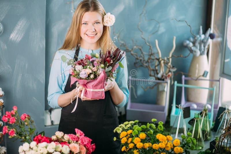 Horisontalfoto av att le kvinnan som ger förberedd blommasammansättning till mannen arkivbilder